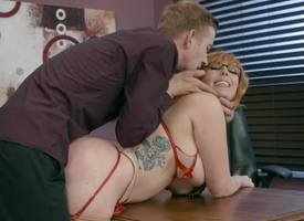 A redhead with glasses with be passed on addition of huge tits is getting fucked on be passed on table